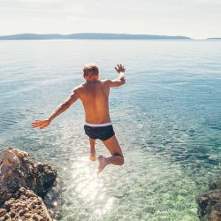 Man jumps in blue sea lagoon water